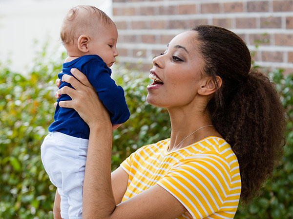 Woman holding up and making faces at her baby.