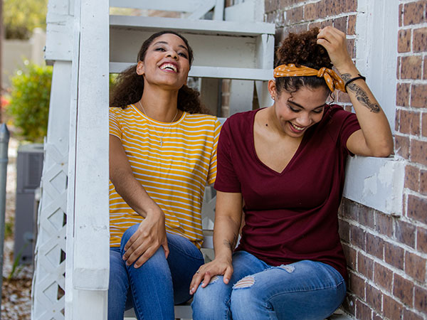Women sitting on porch outside.
