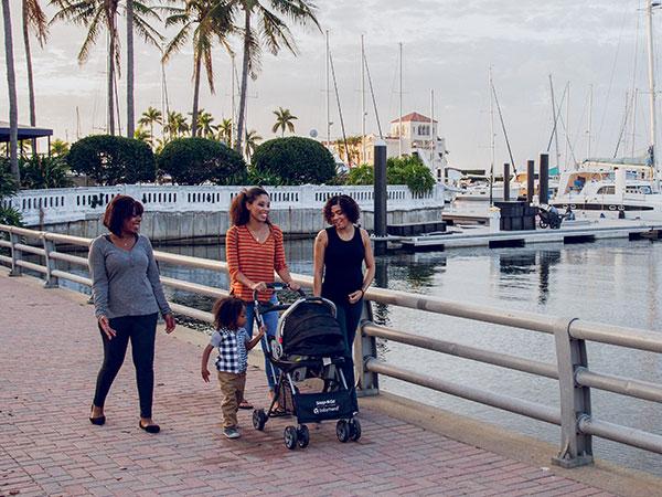 Women outside walking baby by water.