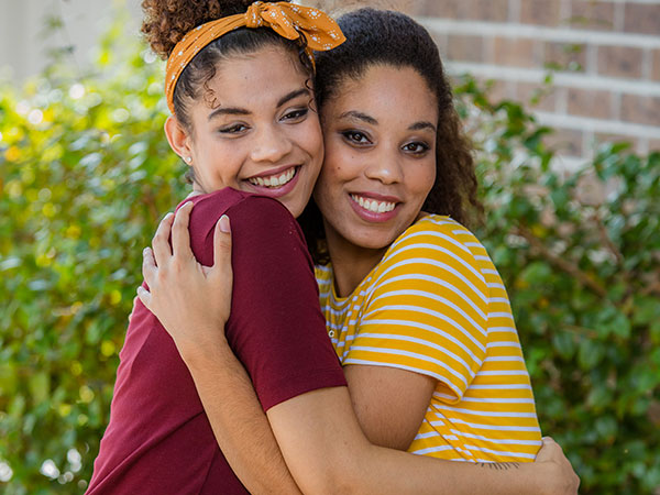Two young women holding eachother.