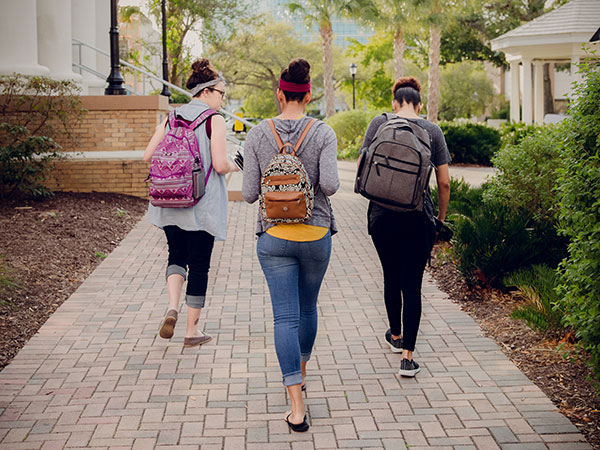 Women walking with backpacks.
