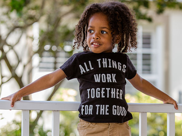 Young child wearing a shirt that says all things work together for the good.