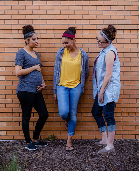 Three young women talking by a wall.
